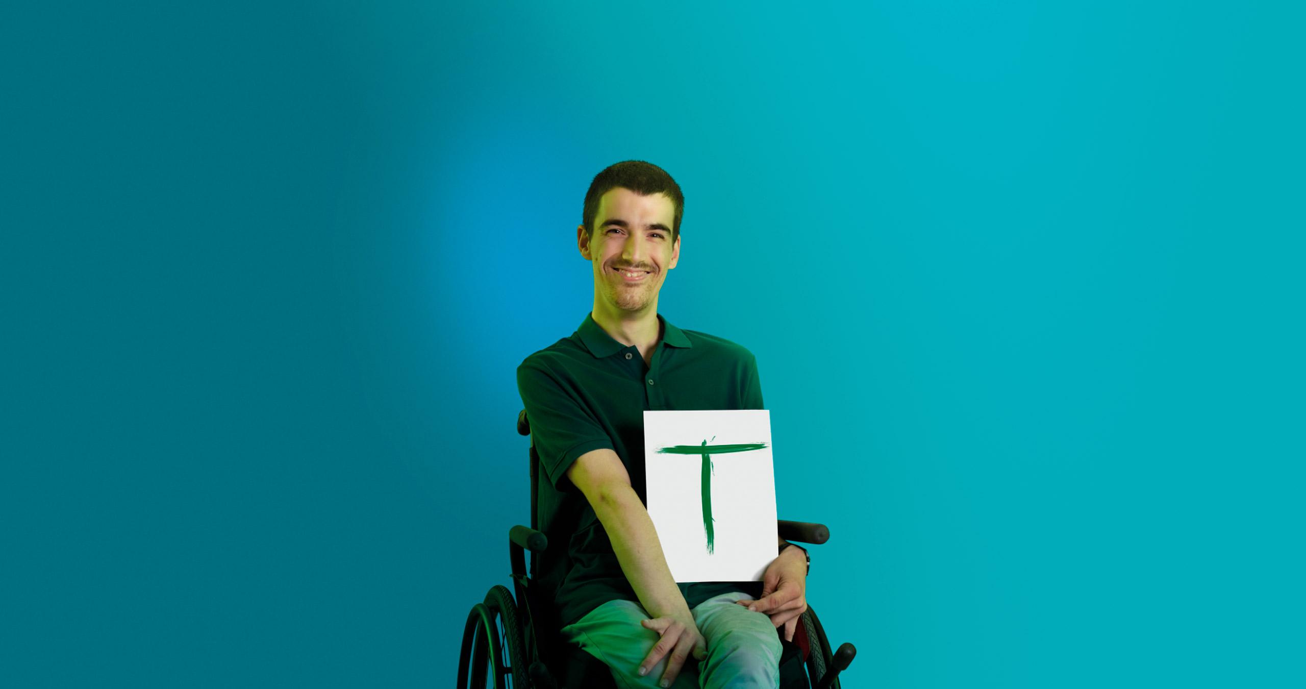 Rapaz em cadeira de rodas com um papel com T