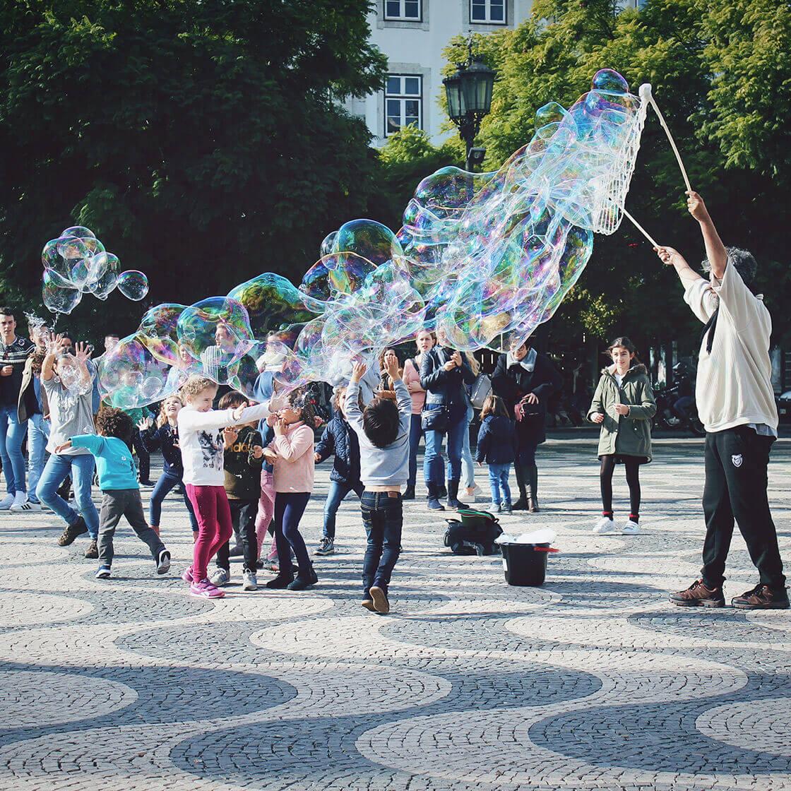 Crianças a brincar com bolas de sabão na Praça do Rossio