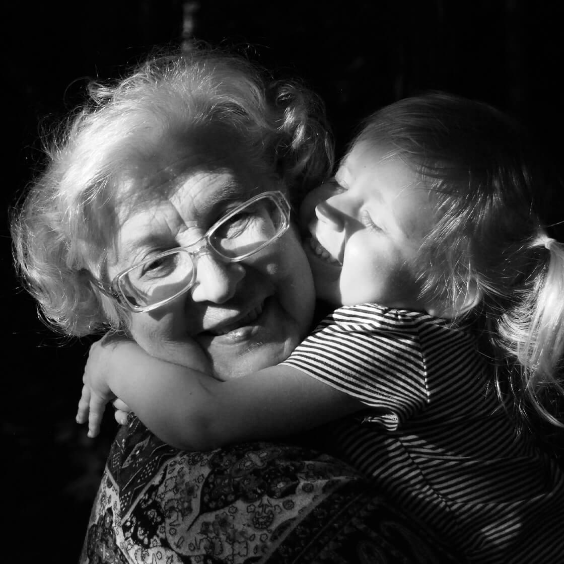 criança abraça idosa