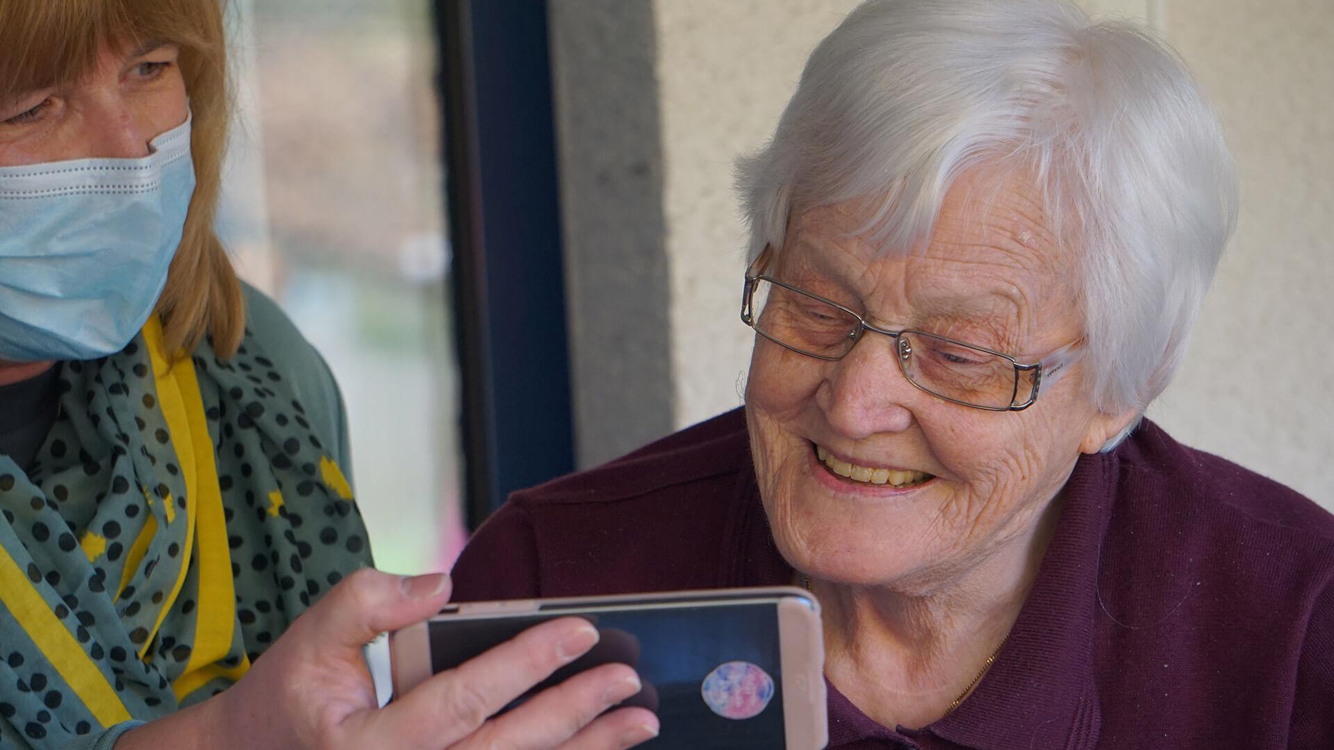 Senhora a mostrar telemóvel a senhora idosa sorridente